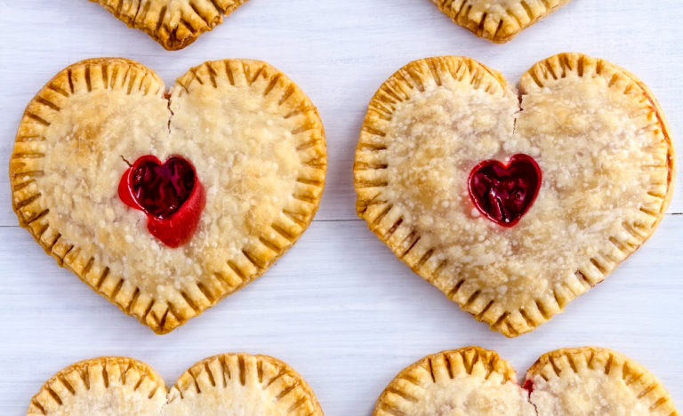 Close up of heart shaped cherry hand pies sitting on white wooden table